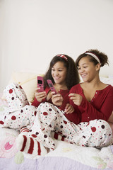 African twin sisters looking at cell phones
