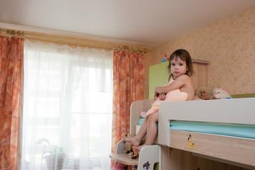 Ребёнок в детской комнате на втором ярусе кровати