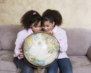 African twin sisters looking at globe