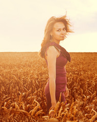 Beautiful woman walking on wheat field