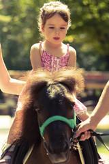 Девочка катается верхом на пони