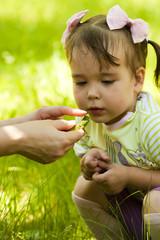 Ребенок смотрит на ящерицу в руках мамы