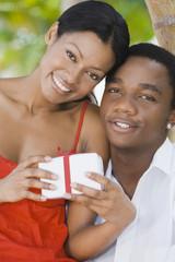 Multi-ethnic couple holding gift