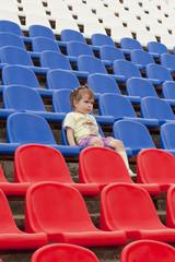 Ребёнок на трибуне стадиона эмоционально наблюдает