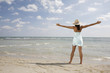 African woman with arms outstretched at beach