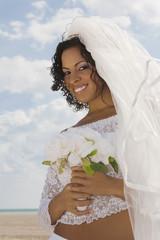 Hispanic bride holding bouquet