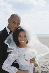 Multi-ethnic bride and groom hugging