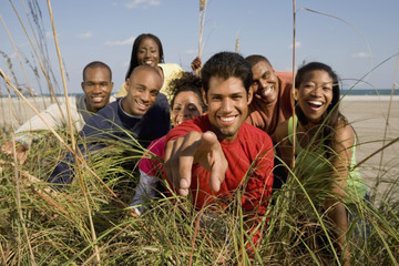 Multi-ethnic friends looking through grass