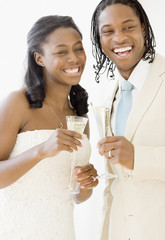 African bride and groom holding champagne flutes