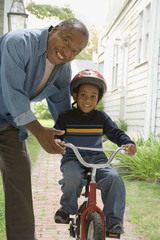 African grandfather teaching grandson to ride bicycle