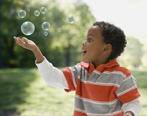 African boy catching bubbles