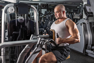 Man doing workout with pull-down machine