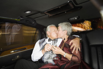 Well dressed senior couple kissing in limousine