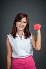 Healthy Asian girl hold a dumbbell and smile