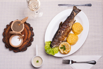 Grilled trout with polenta, lemon, garlic sauce and wine