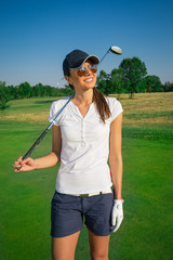 Attractive young woman playing golf