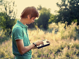 young guy with a tablet outdoors