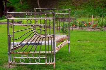 Old metallic bed on the green grass