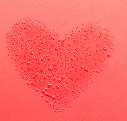 drops of water in the form of heart on a red background