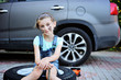 girl with dirty face helps her father to repair car