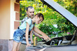 Father teaching his daughter to change motor oil in the car