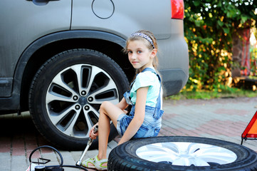 Cute little girl with dirty face helps her father to repair car