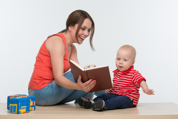 Portrait of young attractive mother and her cute toddler reading