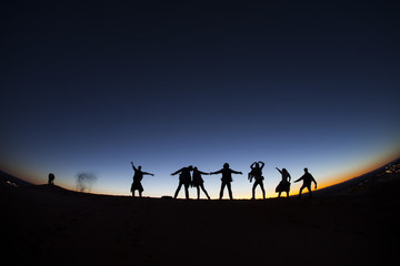 Group of happy people on top of a mountain in the Sahara desert,