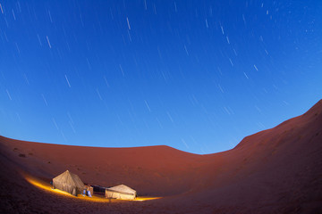 Illuminated camp in Sahara desert in night with moving stars