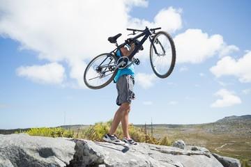 Fit man walking on rocky terrain holding mountain bike