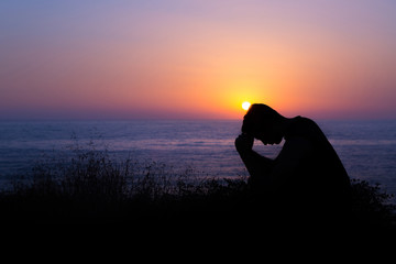 Man Praying by the Sea at Sunset