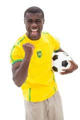 Excited brazilian football fan cheering holding ball