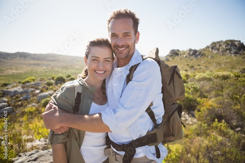 Fotobehang Alpinisme Hiking couple embracing and smiling at camera