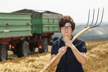 Women farmers with pitchfork works on the field