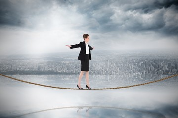 Composite image of businesswoman performing a balancing act on t