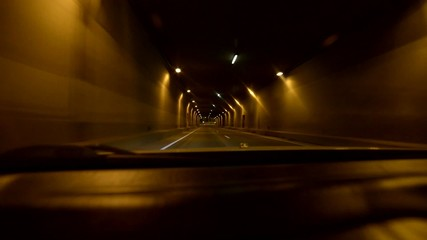 Car driving on highway at night through tunnels.