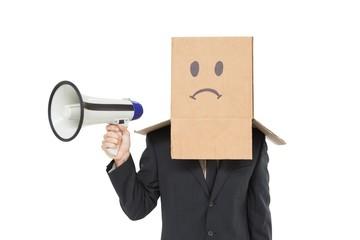 Businessman with box on head holding megaphone