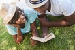 Happy young couple reading book on the grass