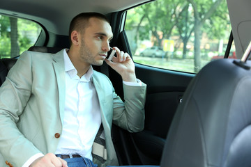 Man sitting in car and spiking phone