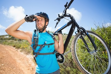 Fit man walking down trail holding mountain bike