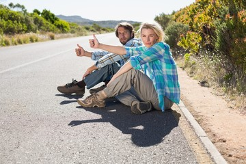 Attractive couple sitting on the road hitching a lift
