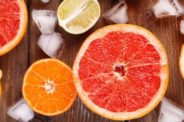 Different sliced juicy citrus fruits with ice on wooden table