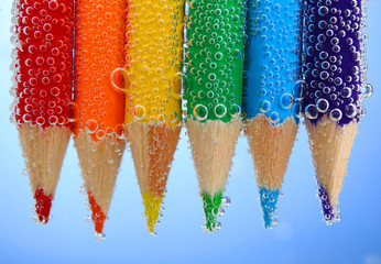 Colorful pencils in water with bubbles on blue background