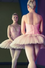 Graceful ballerina standing in first position in front of mirror