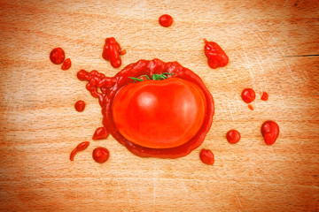 Tomato and ketchup on wooden board