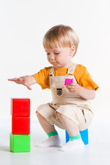 boy is sitting on his haunches and playing cubes