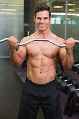 Smiling shirtless muscular man lifting barbell in gym