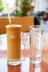 Glasses of frappe coffee and water