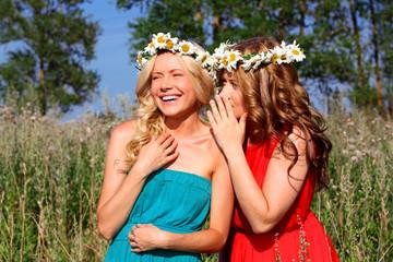 Две девушки с венками шепчутся в поле