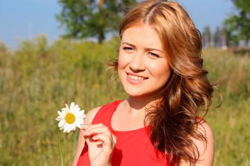 Красивая девушка стоит с цветком на поле и улыбается